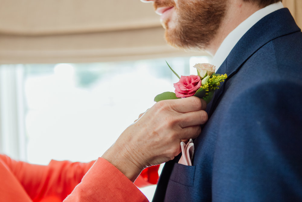 Grooms Mother putting his buttonhole on for Highcliffe Castle Wedding Dorset - Dorset wedding photographer - Hampshire wedding photographer - Documentary wedding photos