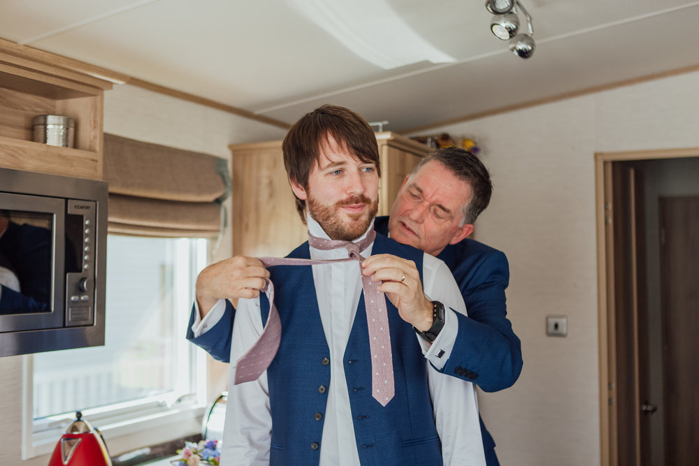 Groom preparations for Highcliffe Castle Wedding Dorset - Grooms Dad doing up his tie - Hampshire wedding photographer - Dorset wedding photographer