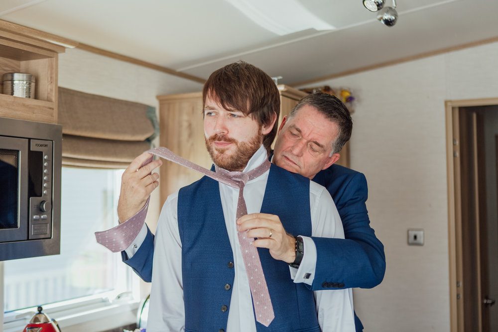 Grooms dad tying his tie on his wedding day - Highcliffe Castle wedding - Dorset wedding photogrpaher