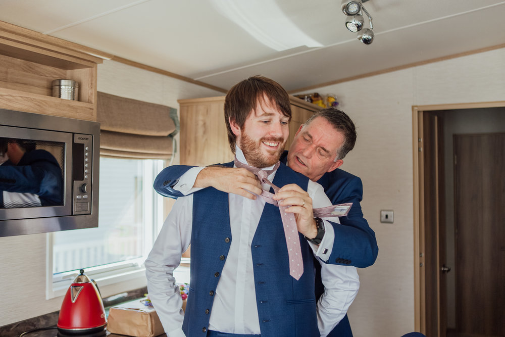 Grooms Dad Tying his tie on his wedding day - highcliffe castle wedding - Dorset Hampshire wedding photographer