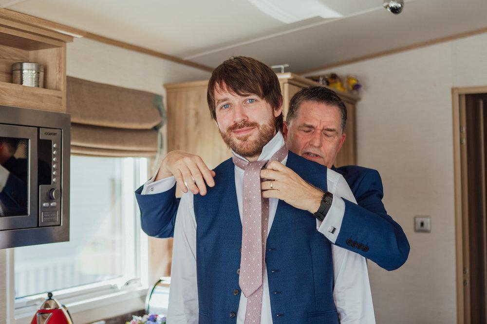 Grooms dad ties his tie - Highcliffe Castle Wedding - Hampshire wedding photographer - Dorset wedding photographer -Groom and His Dad
