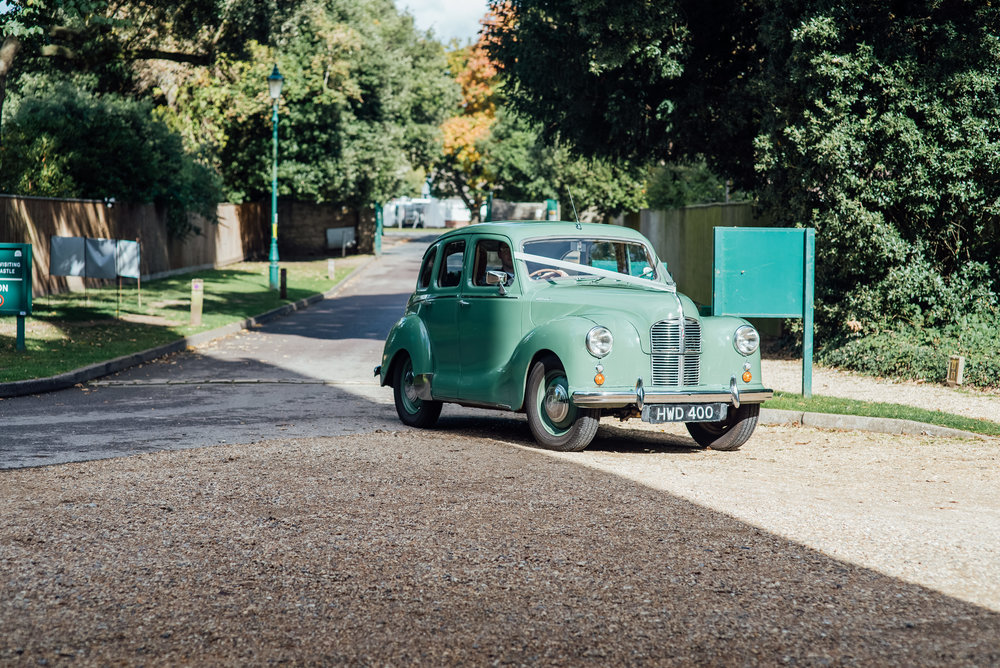 Green vintage wedding car arriving at Highcliffe Castle Wedding Dorset - Amy James Photography - Documentary wedding photographer for Hampshire Surrey and Dorset