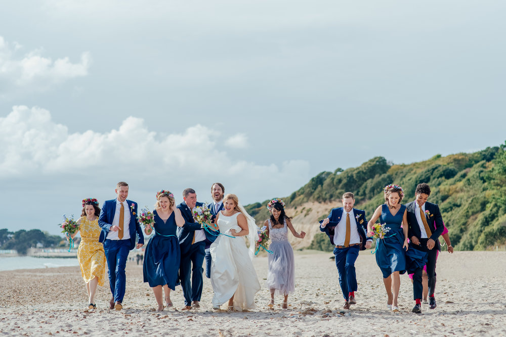 Bride Groom and Bridal Party running on the beach - highcliffe castle wedding - Dorset wedding photographer - Amy James Photography
