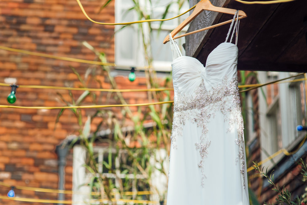 Wedding dress hanging in courtyard at The George In Rye Wedding Venue - Amy James Photography - Hampshire wedding photographer