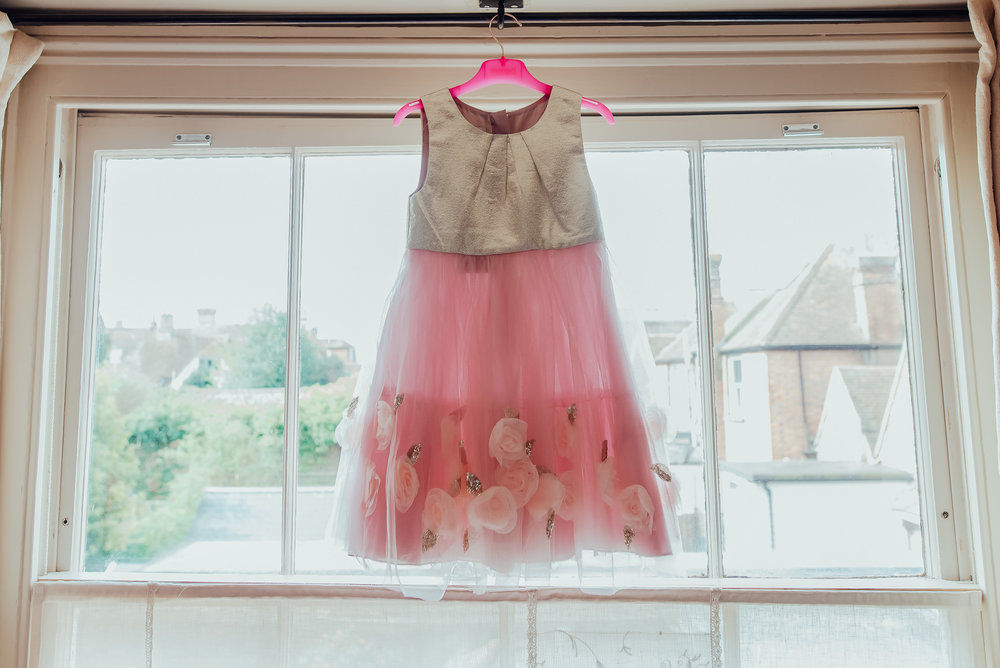 Flower girl dress hanging in the window at The George In Rye Wedding Venue East Sussex