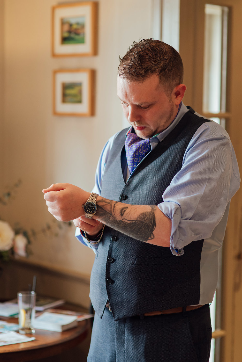 Groom putting watch on at The George in Rye East Sussex Wedding Venue - Amy James Photography documentary wedding photographer