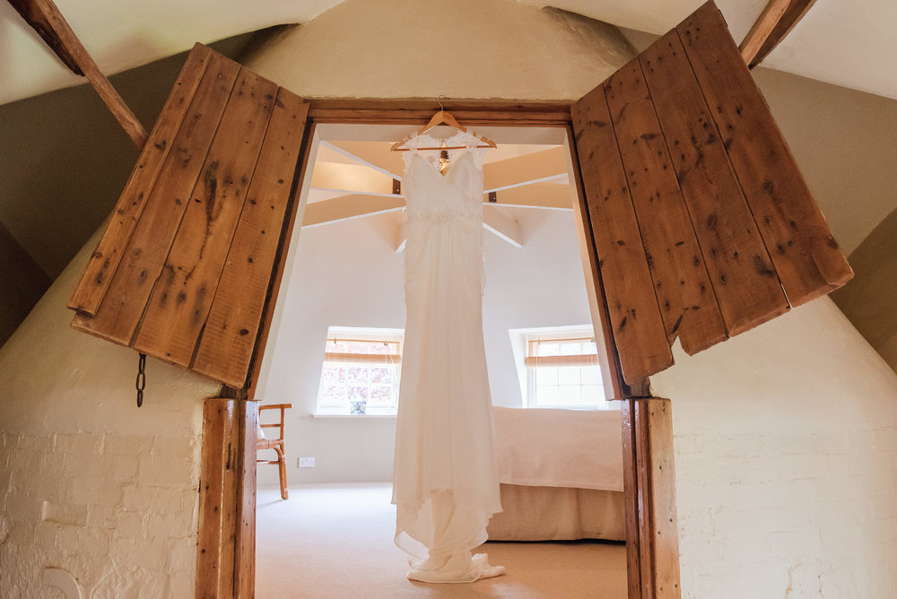 Wedding dress hanging in the barn at bury court wedding venue by Amy James Photographer Wedding-Photographer-hampshire wedding-photographer-fleet