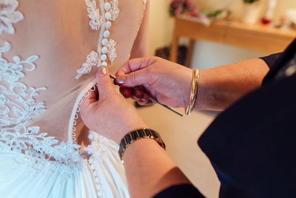 Brides Mother helping her into her wedding dress - Bury Court barn Wedding Venue - Amy James Photography Wedding-photographer-hampshire Documentary-wedding-photographer