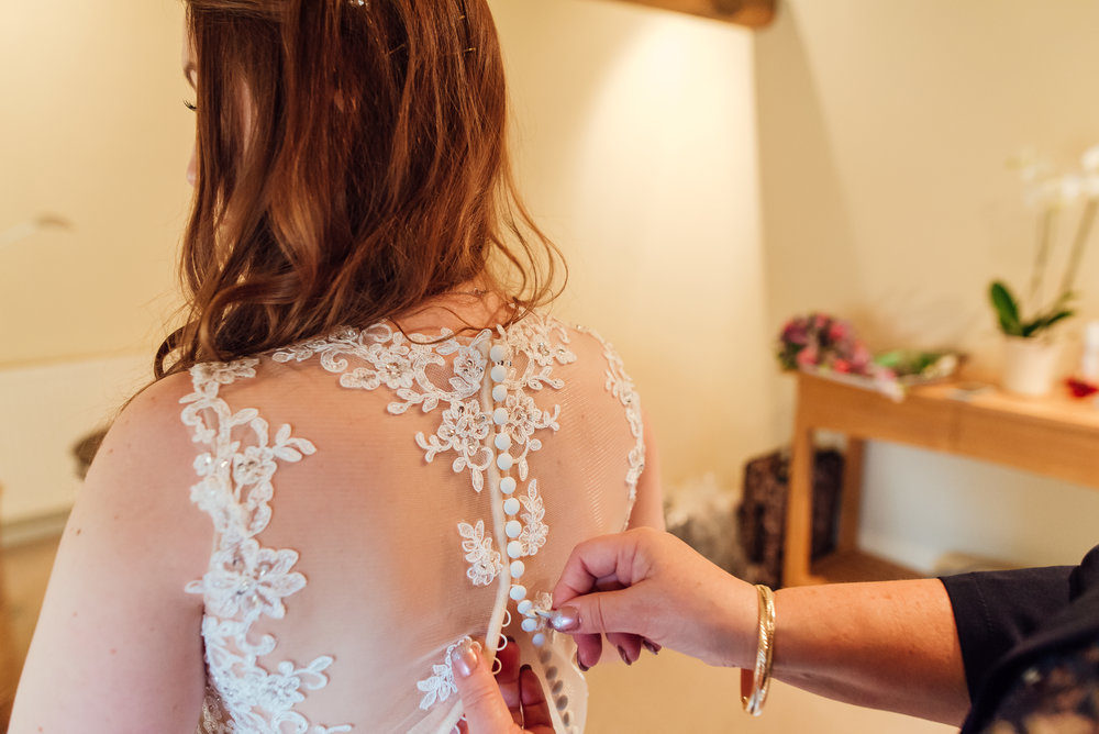 Brides Mum helping her into her wedding dress. Bury Court barn Wedding Venue Hampshire - Amy James Photography Wedding-photogapher-hampshire Documentary-wedding-photographer