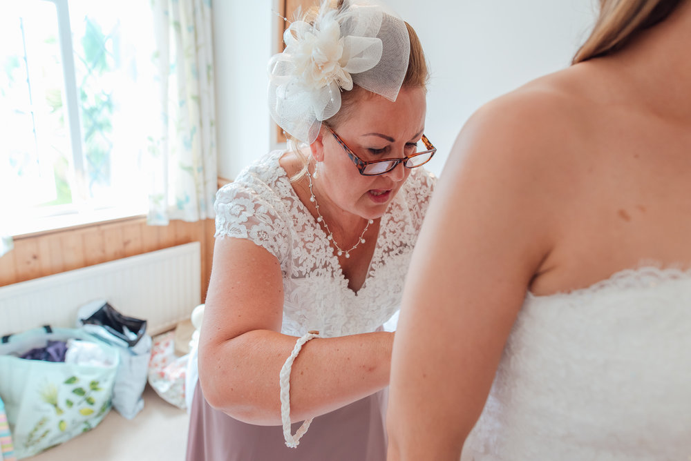 Brides mum doing up her dress / Worplesdon Place Wedding / Hampshire Wedding Photographer / Amy James Photography