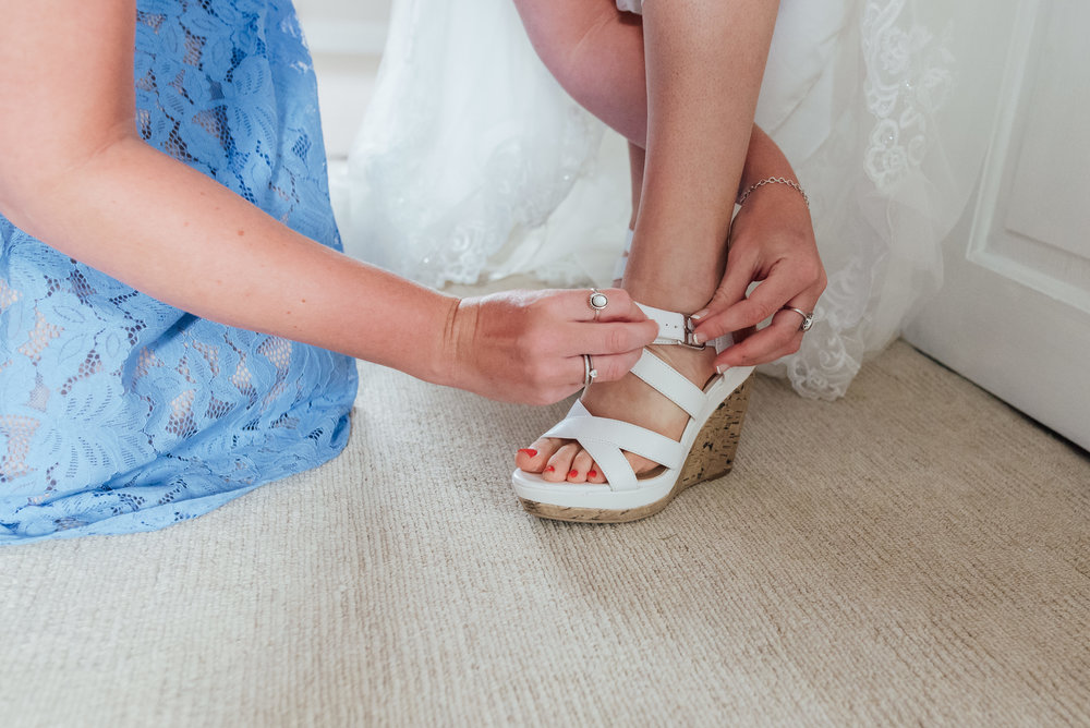 hampshire-wedding-photographer / Amy-james-photography / Hampshire-village-hall-wedding / village-hall-wedding / wedding-photographer-hampshire-surrey-berkshire / rotherwick-village-hall-wedding / Fleet -wedding-photographer / bridesmaid-doing-up-brides-shoe