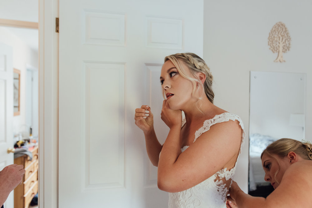 bride-putting-on-earrings / Amy-james-photography / hampshire-wedding-photographer-hampshire