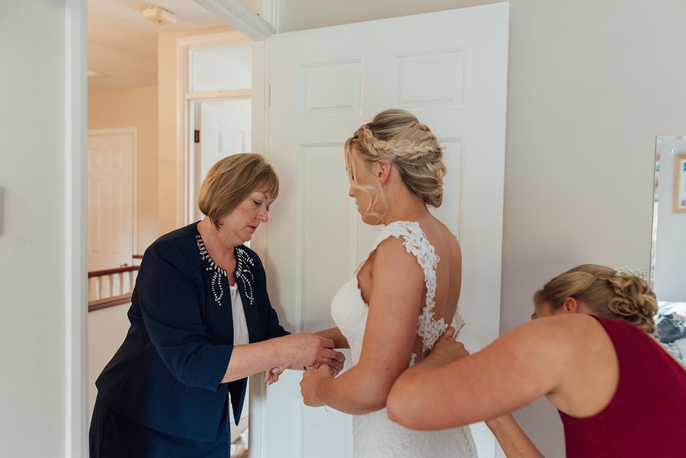 Bride-getting-into-wedding-dress-amy-james-photography-hampshire-wedding-photographer-hampsire
