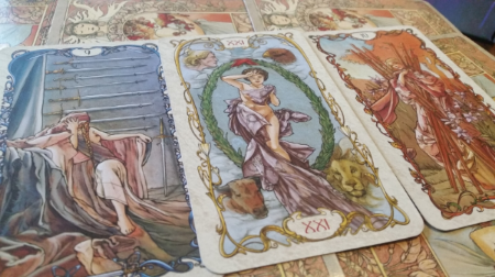This example shows cards from the Tarot Mucha deck: The Nine of Swords, the World, and the Ten of Wands.