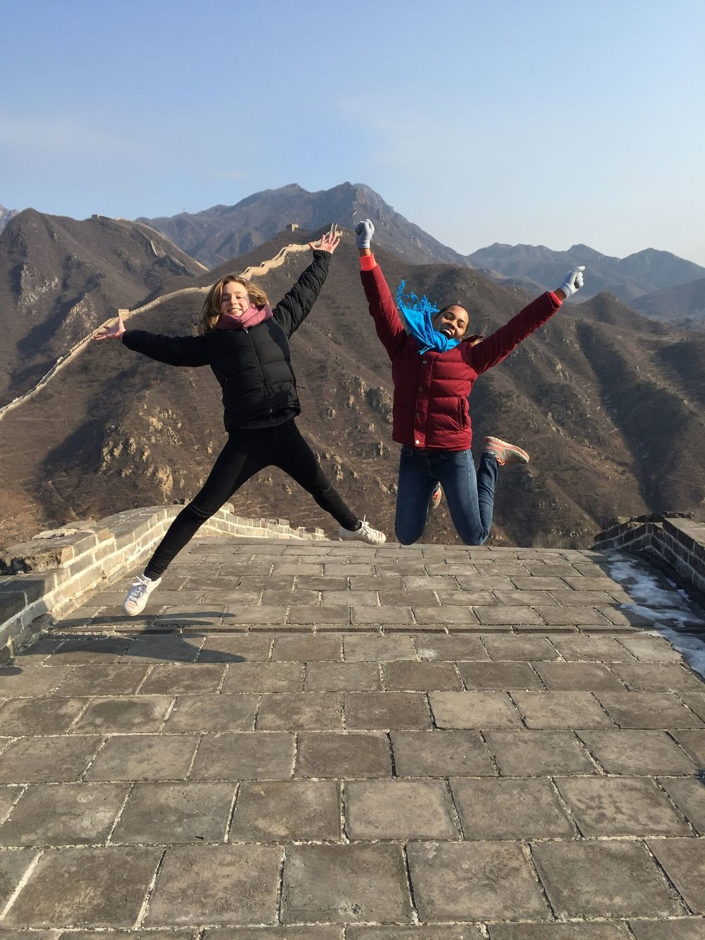 YFU exchange student Maya Hammond, right, jumping for a photo while hiking the Great Wall of China in Beijing for the first time with her European classmate.
