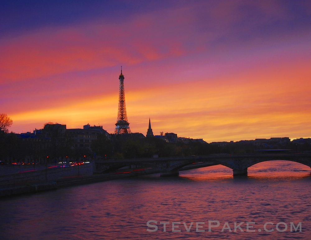 "Via "" The Secrets To Getting Great Photos "", my shot of the Eiffel Tower in Paris with my first DSLR, a Nikon D80, and its 18-55mm kit lens. I was at exactly the right place at exactly the right time, lucked out with some amazing atmospheric effects as the sun set, and that made this photo more than having one lens or another did."