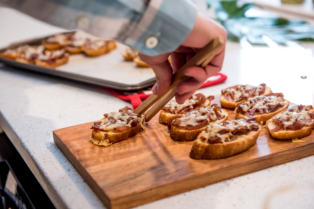 Caramelized Onion and Gruyere Crostini  1 tbsp olive oil 1 tsp chopped garlic 1 large onion, sliced in half circles 1/2 tsp sugar 1/8 tsp salt 4 tsp balsamic vinegar 1/2 cup beef or veggie broth 1/2 tsp thyme leaves  1 cup grated Gruyere cheese 1 loaf Ciabatta bread  Preheat oven to 425 degrees Celsius.  In large skillet, heat olive oil. Add garlic and onion and cook over medium-low heat, stirring occasionally until onions soften. Stir in sugar, salt, then balsamic vinegar. Add broth and simmer for 5-10 minutes or until liquid evaporates. Stir in thyme leaves and remove from heat.  Remove ends of loaf and slice into 16 pieces. Put a spoonful of onion mixture on each slice and sprinkle with cheese.  Bake in oven on parchment lined baking sheet until cheese is bubbling and golden (10 minutes). Serve immediately.