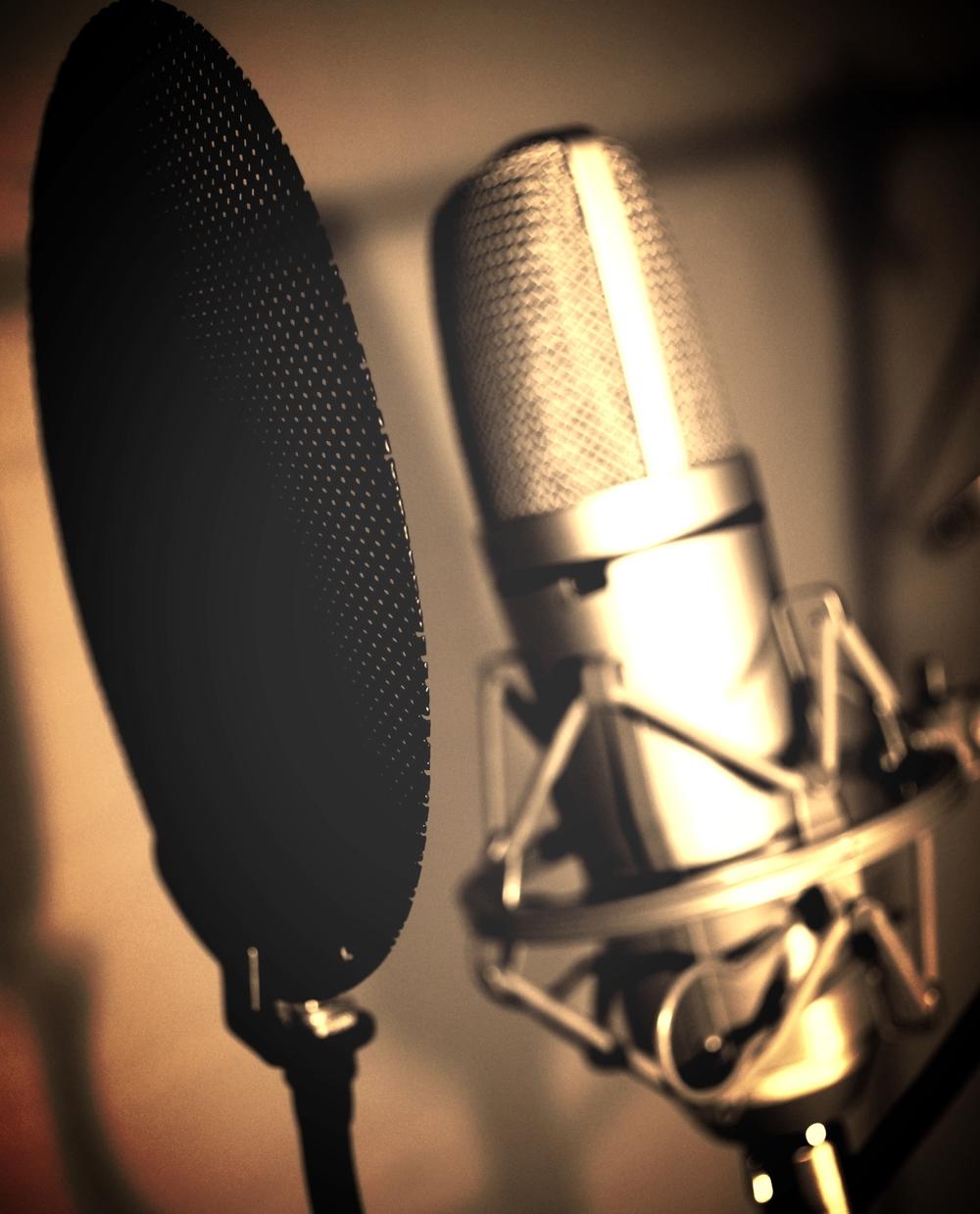 Sølvfarget stormembranmikrofon foran et sort popfilter, klar til innspilling