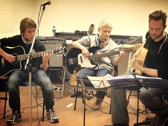 Unge elever ved Feedback Studios på akustisk gitar og bass. Elevene mottar instruksjon fra gitarlærer Stig Blindheim Hansen.