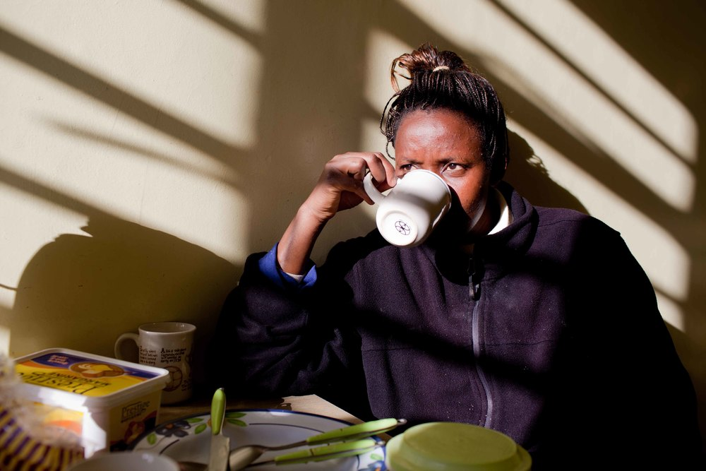 Grace Klomo, one of the two night nurses at sips her tea shortly after finding out that one of the patients, Mary Wangui, died earlier that morning. Grace has worked 12-hour night shifts at the hospice for one year, which can be difficult emotionally as patients often pass away during the night rather than the day.