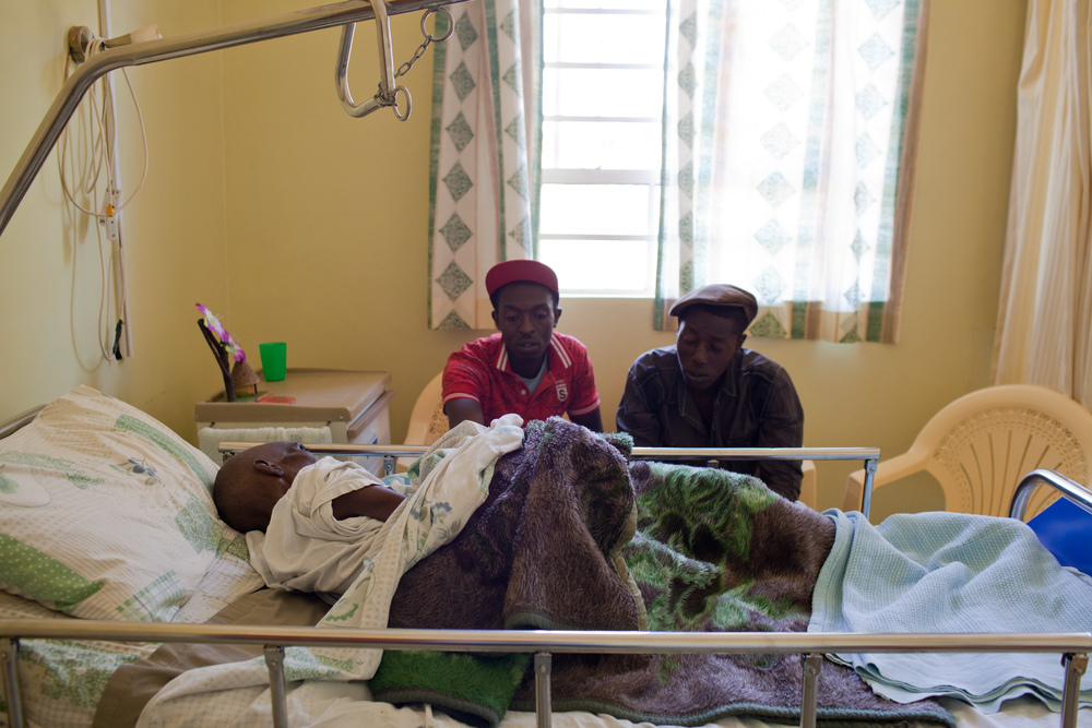 "Peter Waweru, 27, and his nephew, David, visit their father and grandfather, respectively, David Waweru, 61, at the hospice. ""We are happy with the care that he gets here,"" Peter said. ""Because I don't have a stable job and work different days, I wouldn't be able to do this at home."""