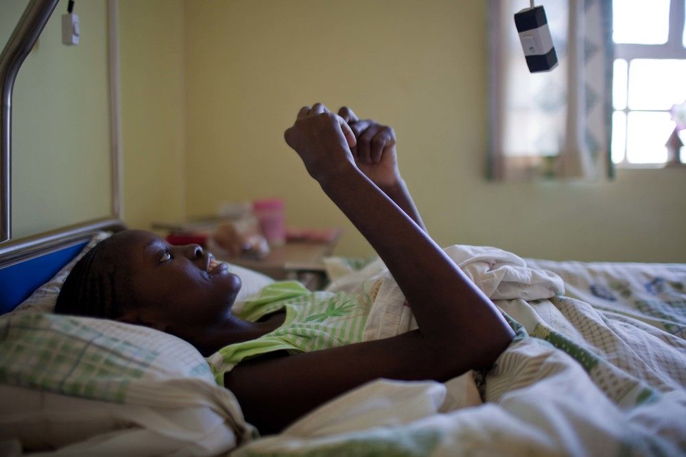 Florence Akoth, 29, unwraps a Kinder chocolate before settling down for the evening. Florence and the other patients tire easily. Their day exists primarily from 7 AM to 2:30 PM when they can go outside, watch television, or rest in bed.