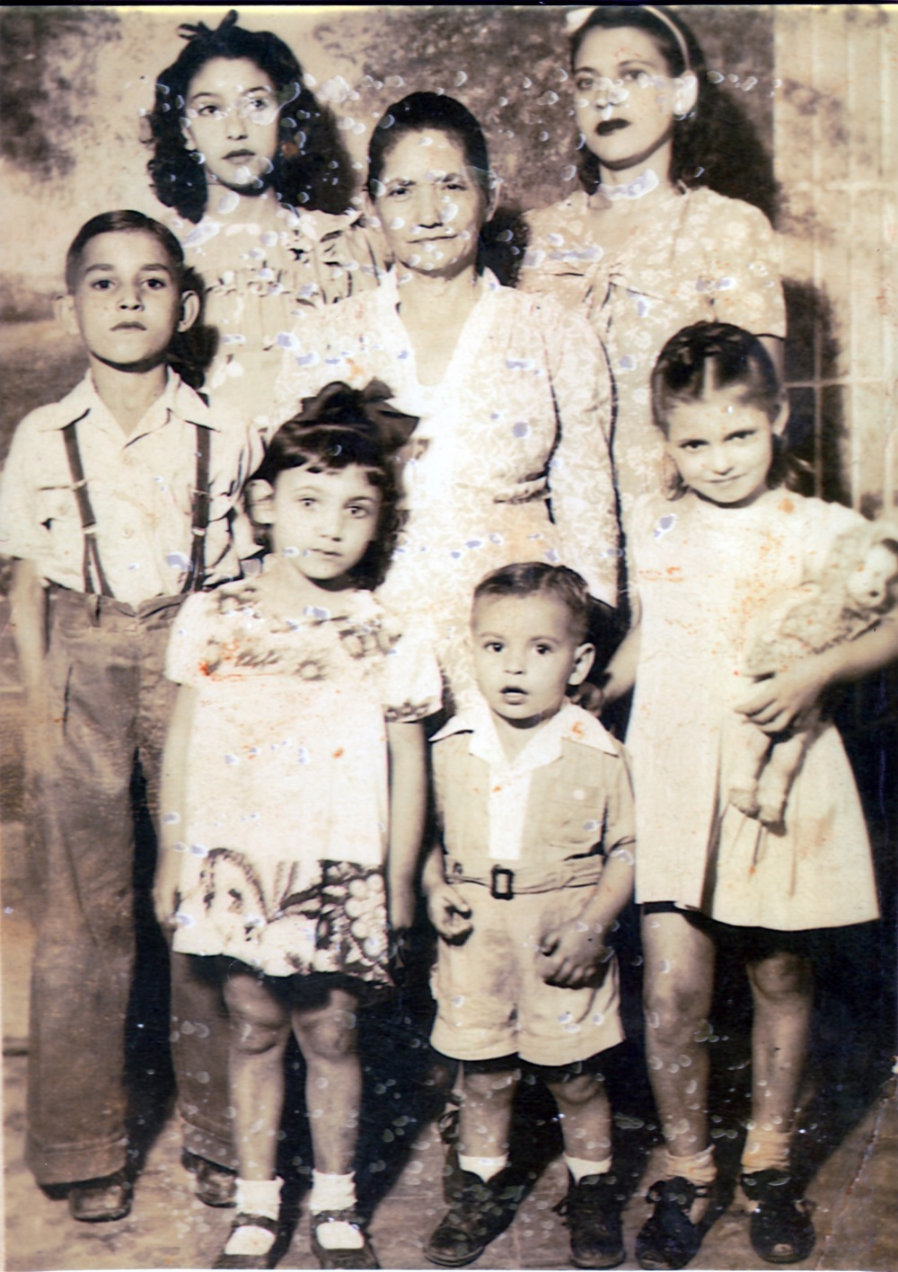 An early photography of my grandmother's family. Martha is pictured in the first row on the right, holding the doll. Her younger sister Juana is in the front row with the bow on her head.