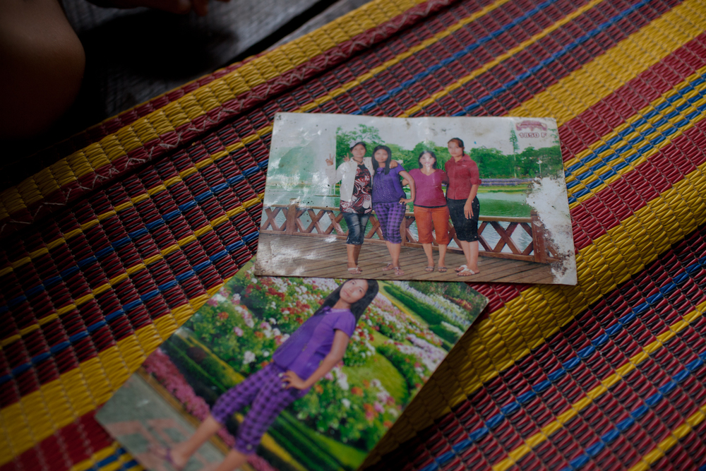 Lin Lin Tun shows off photographs of herself taken at a photo studio before she was married. In Myanmar, it's quite popular for young people to get professional photos taken at a studio in Yangon before big life events, such as moving away or getting married. Backdrops include pagodas, cityscapes, and beaches - these images are a visual way to transport the Burmese from their restricted lives in Myanmar to the outside world.