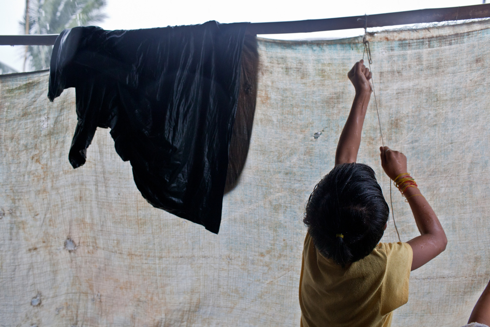 At the onset of a heavy rainstorm, Pyae Paing Paing raises the family's  moth-holed tarp to protect the second floor of the home from rain. During the monsoon season in Burma, rain lasts from only a few minutes to hours. Storms create numerous problems for the people in the rural areas surrounding Yangon, as many people have open homes without windows or proper walls.