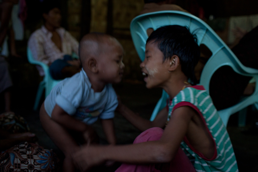 Thin Htet Aung laughs beside his younger cousin, Kyi Khine, in an attempt to cheer him up. A toddler, Kyi Khine, suffers from intestinal issues and is often restless and crying, despite his mother's efforts using traditional medicine. In the township that they live in, there are several clinics run by well-qualified doctors. The quality of health care in their area is not a problem, the problem for the family is that they are not able to afford treatment.