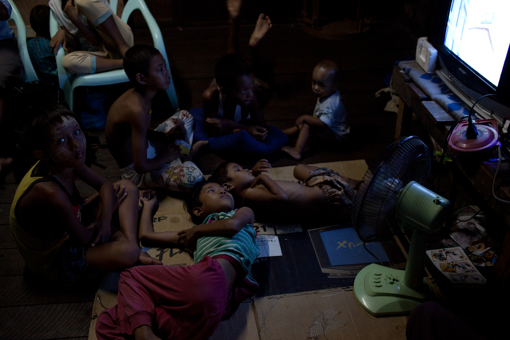 After eating their daily dinner of white rice and broiled chicken, the kids lie around the television to watch Tom and Jerry. Although they've had the TV for over a year, they still use its box as a mat for sleeping. The television continues to sit in the styrofoam container that it came in.