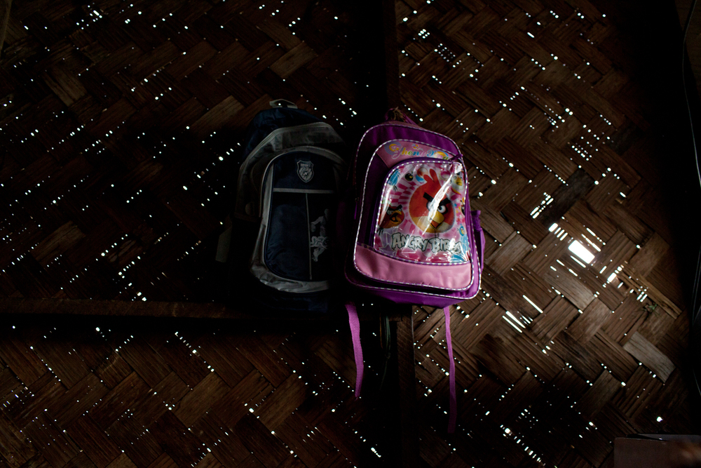 "A boy's backpack and a girl's backpack hang side-by-side on a recently repaired wall in the home. When Cyclone Nargis hit in 2007, two pieces of their corrugated tin roof blew away and they had to move into an abandoned hut down the road for refuge from the storm. Four days after the hurricane passed, Daw Than Yi's husband, the head of the household, become ill and died. Since his death, it has been difficult for Than Yi to support her children through school and she had to learn her husband's trade of selling groceries. Every day, she says, is a ""struggle."""
