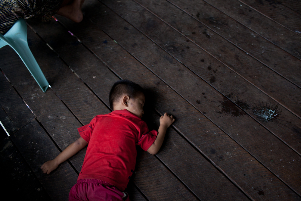 Ar Kwae naps next to a puddle of spilled yogurt. The adults often feed the younger children small cups of plain yogurt mixed with coffee for lunch. This simple is cheap, and helps save the rice, meat, and fish paste for the older children and adults.