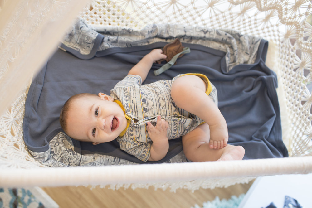 Tej, one of our first baby models, is wearing Finn + Emma's Tribal body suit, happy gumming on Finn + Emma's beloved wood tethers! Also pictured is the Totem Blanket, also Finn + Emma... 100 % Organic cotton & 100% adorable!