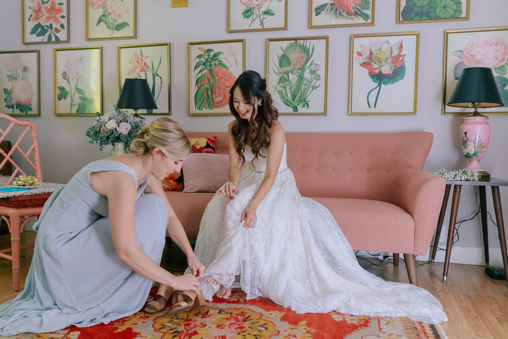 C&M helping the bride with her shoes in the pink room.jpg