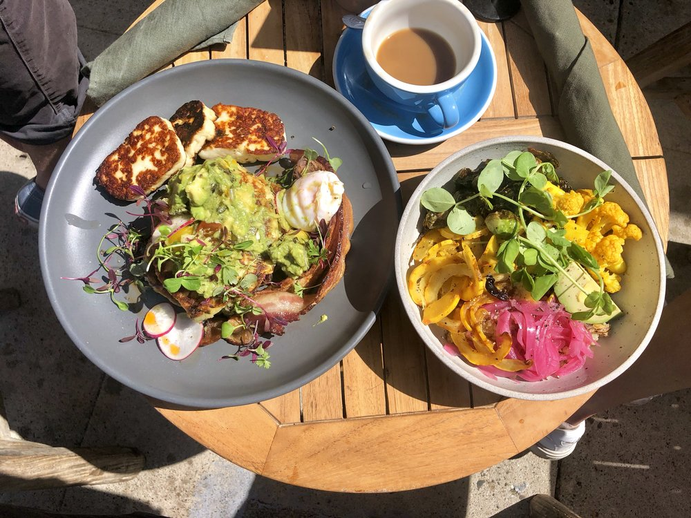 corn fritters // stacked corn fritter, poached egg, charred avocado salsa, fresh greens, bacon, halloumi  harvest bowl // charred brussels sprouts, turmeric roasted cauliflower, delicata squash, shaved almonds, pickled onion, avocado, quinoa, roasted almond vinaigrette