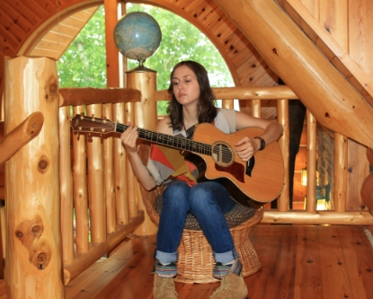 Alison Rose playing guitar at the log cabin