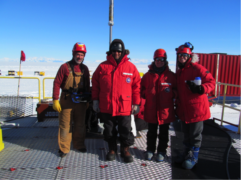 The author (right) and colleagues on deck in Antarctica next to a half-mile-thick borehole through an Antarctic ice shelf.