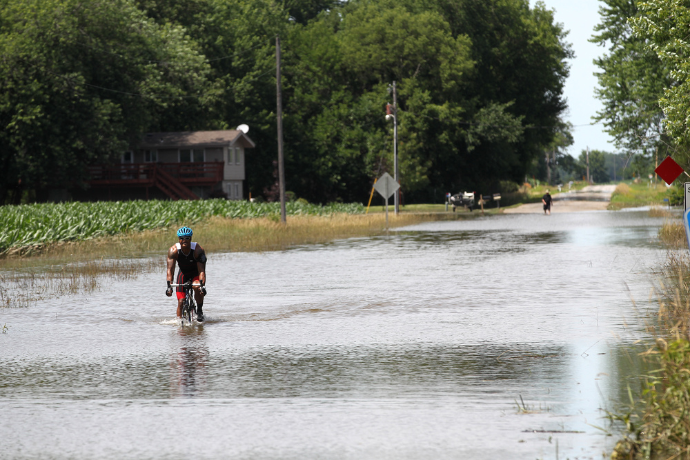 Lance Tillison bikes through a flooded road off of Highway 22 in Riverside as he makes his way back to Iowa City.