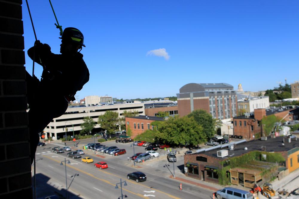 Iowa City firefighter Jason Jordan rappels down the Court Street parking ramp during a high-rise emergency training.