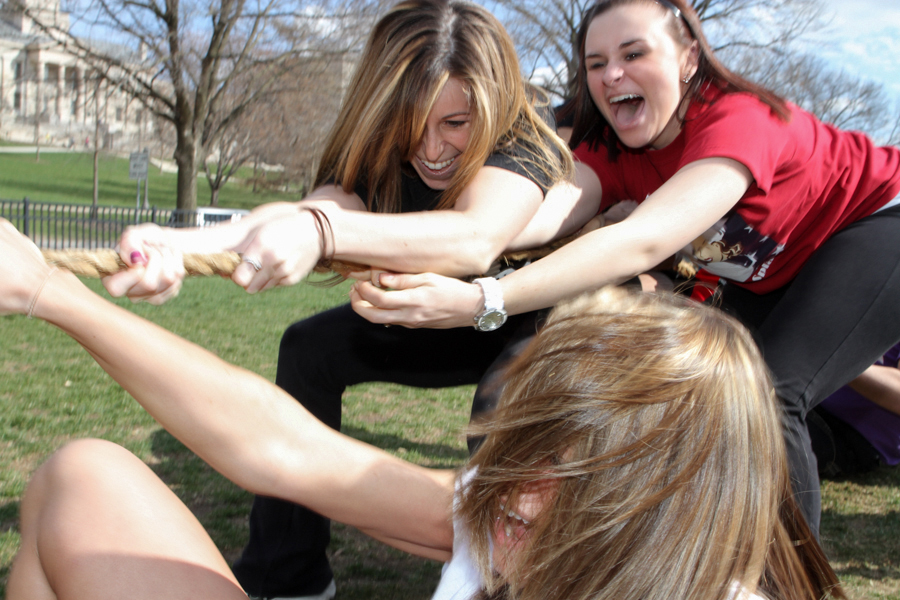 Delta Gamma sophomores Shantel Kahrs, bottom, Megan Dougherty, top left, and Mikayla Logan get pulled to the ground during a tug-of-war in the Greek Olympics.