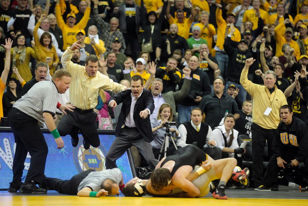 Iowa head coach Tom Brands, left, and associate head coach Terry Brands, second from left, leap in the air as Mike Evans throws down Ohio State's Nick Heflin for a 9-4 overtime win.