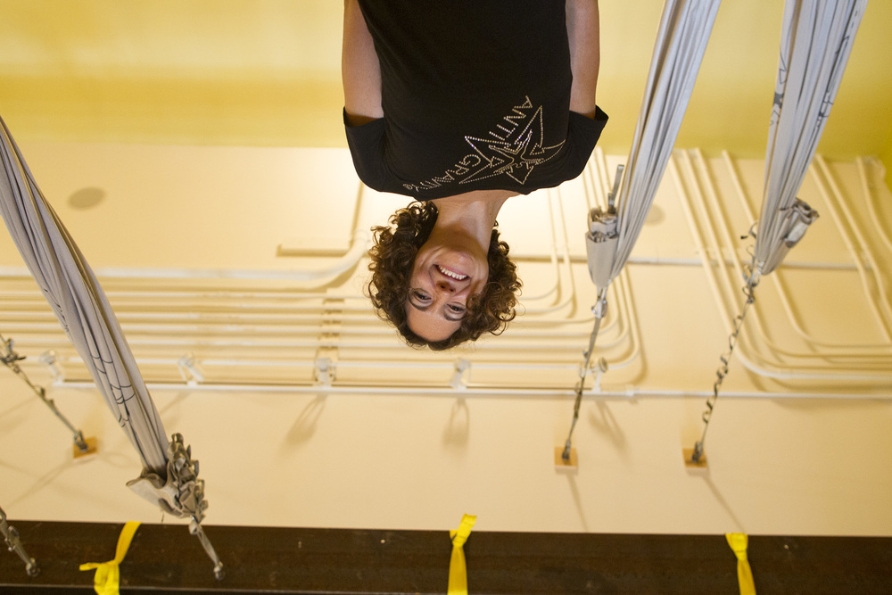 Yoga instructor Marcie Evans, seen from an inverted angle from an AntiGravity Yoga hammock, poses for a photo at Serenity Yoga & Pilates Studio in Iowa City.