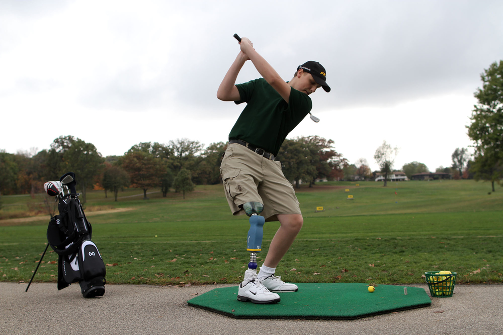 Drew Wall practices at the Ellis Golf Course driving range. Wall's prosthetic leg has a customized torquing mechanism at the ankle to allow Wall to fully twist while swinging his club.