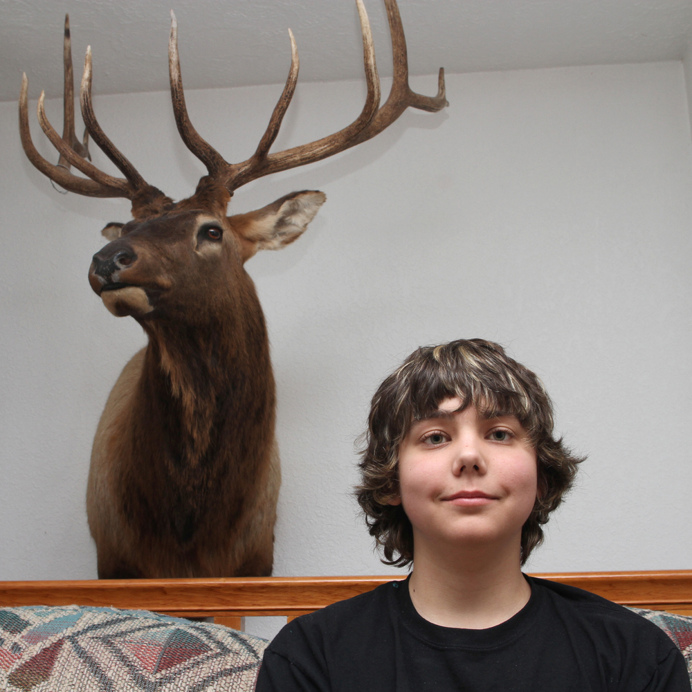 Dillyn Mumme, 15, poses by his 10-point buck in his home in Mount Pleasant.