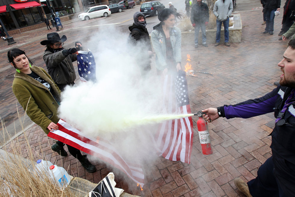 FedEx employee Matt Uhrin extinguishes a set of American flags being set on fire by protesters.