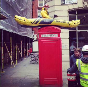 George in kayak on top of London phone box