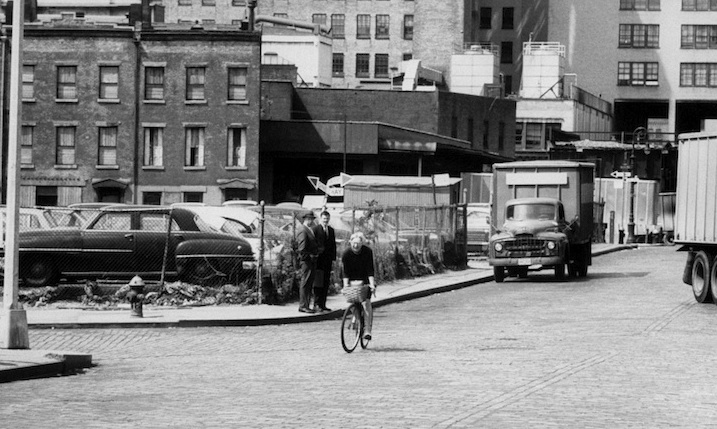 Jane Jacobs cycles past the site of West Village Houses, a low-rise, mixed-income housing development that she championed, in 1962. Getty Images.