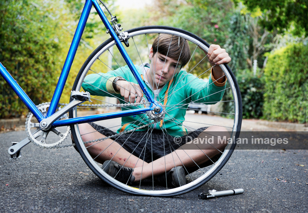 Teenage boy fixing his bicycle.