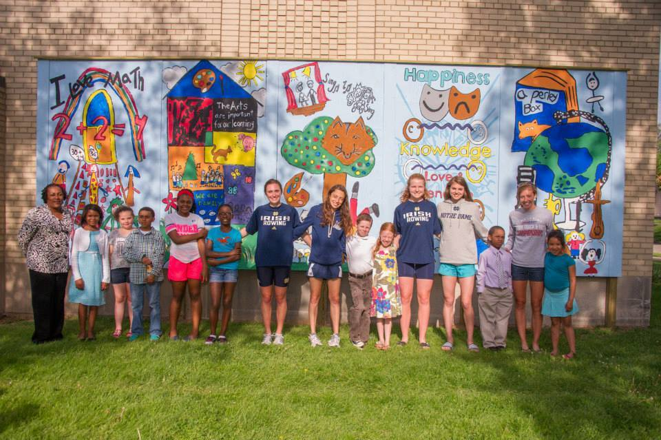 2013-14   SAAC   worked with nearby Perley Elementary School in a project to make their Arts Academy building match the dedication and passion of the arts that exists on the inside of the building. Student-athletes dedicated their Sunday afternoons for 4 weekends to go over to the school and work with their students to brainstorm, draw, then paint images on boards that would then be hung on the north facing side of their school. The process bonded elementary school students to Notre Dame student-athletes and allowed them to learn from one another about creativity, goal setting, hard work, and dedication.
